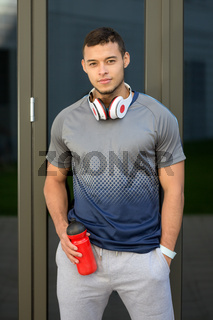 Young latin man water bottle runner portrait format running sports training fitness