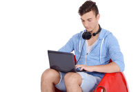 Close up of young man sitting in red pouf using laptop