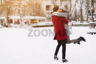 A young guy and a girl are hugging each other