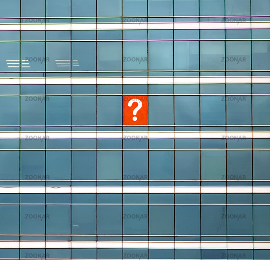 The symbol of the query mark on the building's window. The glass facade of skyscraper with many identical windows and one window with question sign.