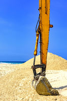 Yellow excavator at beach