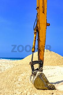 Yellow excavator at beach