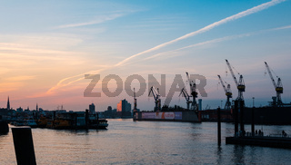 Hamburg Harbor at sunset or sunrise, Freight shipping cranes