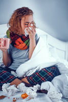 Sick girl in scarf sits on bed and blows her nose