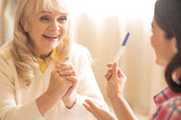Smiling senior women sees the results of pregnancy test