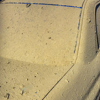 Blue car crusted with dry mud