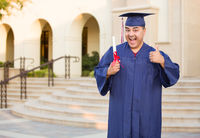 Hispanic Male With Deploma Wearing Graduation Cap and Gown On Campus