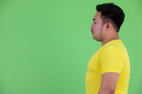 Profile view of young handsome overweight Asian man