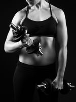 Woman is exercising with dumbbells.