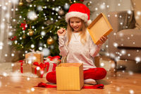 excited girl in santa hat opening christmas gift
