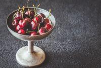 Fresh cherries in vintage silver vase
