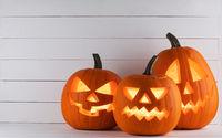 Three glowing Halloween pumpkins
