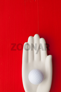 Detail of artifical hand with golf equipments