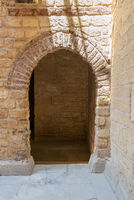 Vaulted open wooden grunge door in bricks stone wall