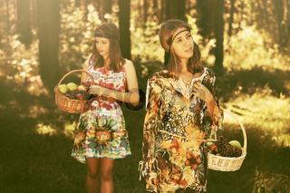 Happy young fashion girls with a fruit basket walking in summer forest