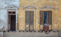 Aged abandoned  vintage grunge house facade with broken windows and weathered shutters