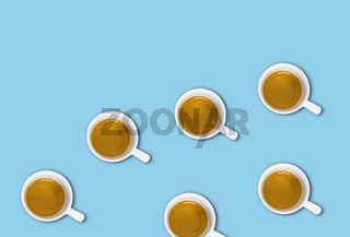 minimalist pattern with a top view of a group of coffee cups on a light blue pastel table