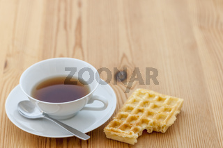 Teacup with spoon and biscuit flat angle view