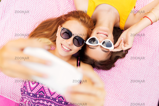 teenage girls in sunglasses taking selfie
