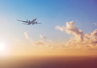 airplane flying above  ocean with sunset sky background   - travel concept -