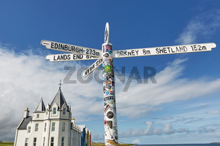 Britains lands end sign at john o'groats in scotland with blue skies and ocean and grass in background. Has many stickers on post.