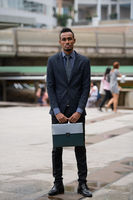 Happy young African businessman with briefcase outdoors