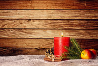 Kerze mit Weihnachtsdekoration vor Holzwand