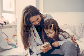 Mom and daughter are looking at the smartphone