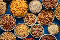 Assortment of different kinds cereals placed in ceramic bowls on table