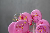 Pink caramel candies on sticks for party. Details