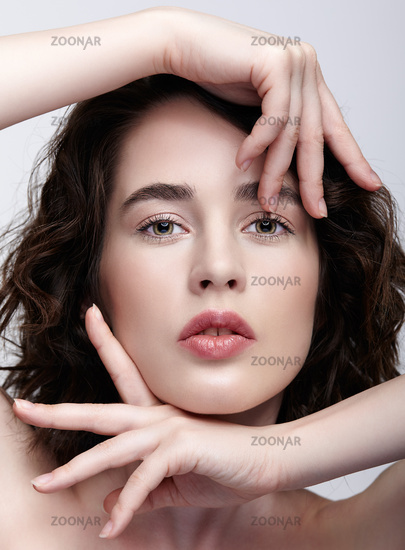 Closeup beauty portrait of young woman with hands near face