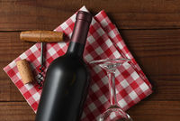Closeup High angle view of a red wine bottle on a red and white checkered napkin