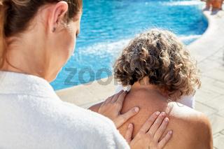 Physiotherapeutin massiert Rücken einer Frau