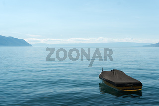 mountain and lake landscape with a single boat and copy space
