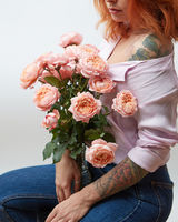 A bouquet of pink roses in a vase holds a girl with a tattoo on a gray background with copy space. St. Valentine's Day