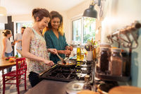 Mixed group of friends have fun while cooking a meal in kitchen