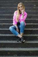 Pensive blonde posing outdoors.