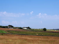 a panoramic view of grass covered fields with cows near blackshaw head in west yorkshire with distant farmhouses and pennine hills against a blue summer sky