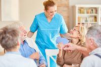 Altenpflegerin betreut Senioren beim Kartenspiel