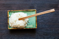top view of boiled rice with chopsticks on plate