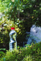 Transparent plastic A bottle of clean water with a red lid stands in the grass and moss on the background of a rugged mountain river. The concept of pure natural drinking water