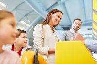 Familie mit Kindern am Check-In Schalter