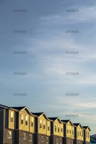 Townhouses on a neighborhood under blue sky and clouds on a sunny day