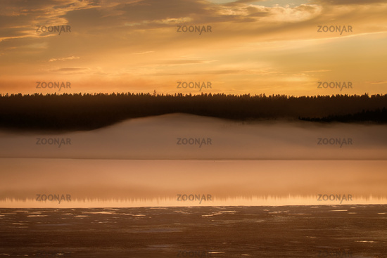 Misty calm evening on the forest lake, sunset