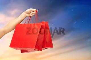 close up of male hand holding red shopping bags