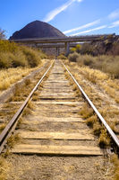 Train tracks in the desert with road and hill