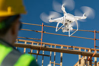 Female Pilot Flies Drone Quadcopter Inspecting Construction Site