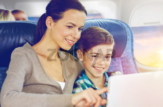 happy family with tablet pc sitting in plane