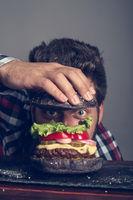 Man cooking black burger