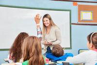 Lehrerin im Unterricht stellt Fragen